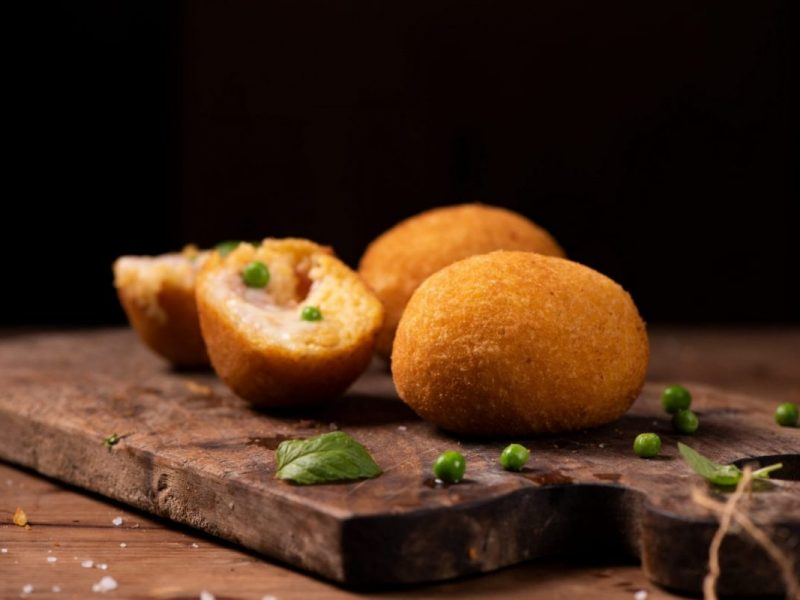 Sicilian Arancini made with fried risotto cheese ham and peas